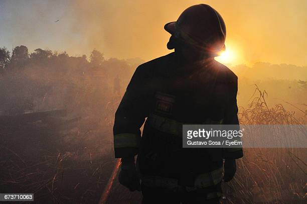 firefighter walking on field against sky during sunset - fire protection suit stock photos and pictures