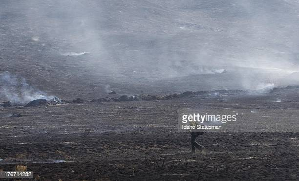 A firefighter walks across a blackened field near homes on Croy Road and the Rotorun ski hill west of Hailey Idaho Saturday August 17 2013 The Beaver...