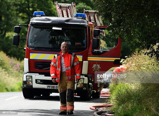 A firefighter walks along a lane close to where a wood treatment works went up in flames in Bosley north England on July 17 2015 Four people are...
