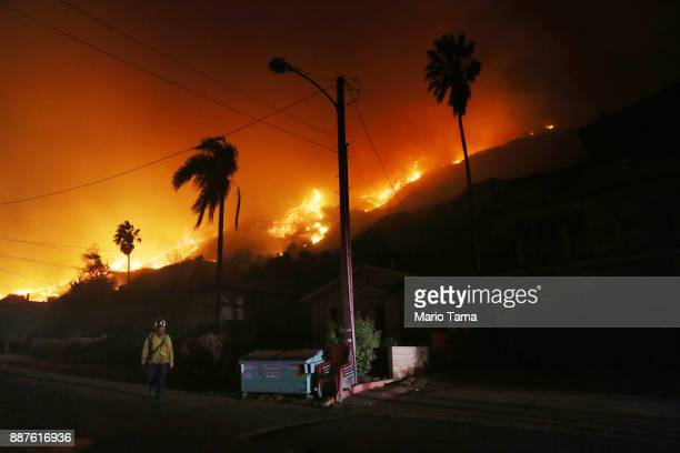 A firefighter walks as a section of the Thomas Fire burns down a bluff toward homes on December 7 2017 in La Conchita California Many evacuation...