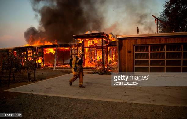 A firefighter walks by a house as it burns during the Kincade fire in Healdsburg California on October 27 2019 Powerful winds were fanning wildfires...