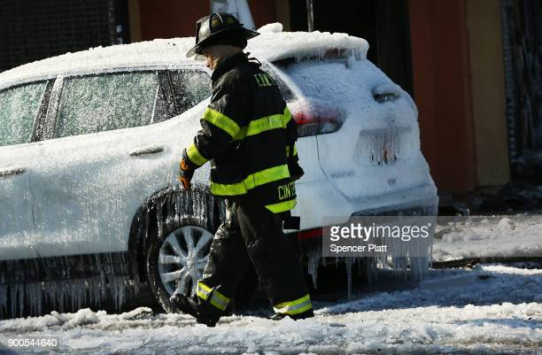 A firefighter walks by an iced over car after fighting a 7alarm fire on January 2 2018 in the Bronx borough of New York City The fire which started...