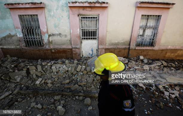 TOPSHOT A firefighter walks in front of a house damaged during a 49 earthquake in Valencia Carabobo State Venezuela on December 27 2018 A strong...