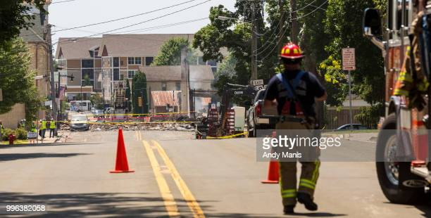 A firefighter walks on a street after a gas leak explosion destroyed at least four buildings on July 11 2018 in Sun Prairie Wisconsin One firefighter...