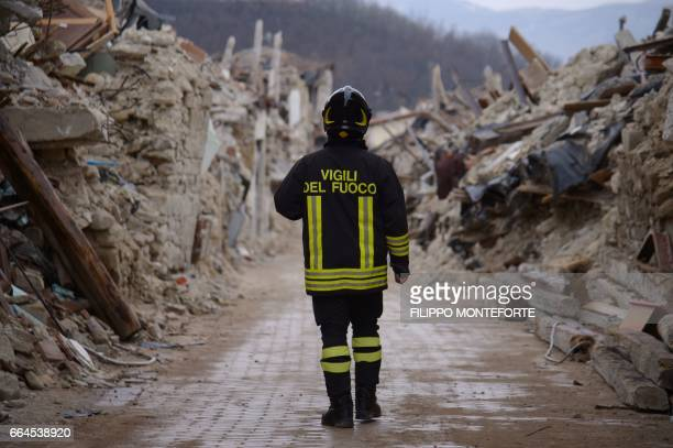 Firefighter walks on April 2, 2017 along collapsed buildings in the historic center of Amatrice eight months after a 6.0 quake completely destroyed...