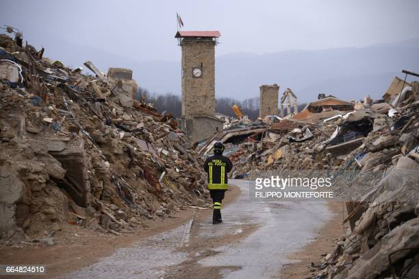 A firefighter walks on April 2 2017 along collapsed buildings in the historic center of Amatrice eight months after a 60 quake completely destroyed...