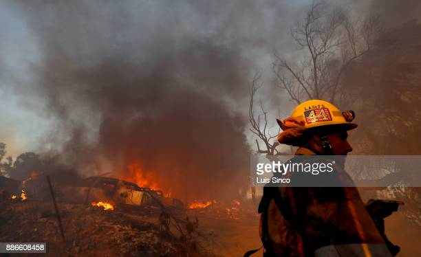 A firefighter walks past a burning house in the path of the Creek Fire near the intersection of Johanna Avenue and McBroom Street in Shadow Hills on...