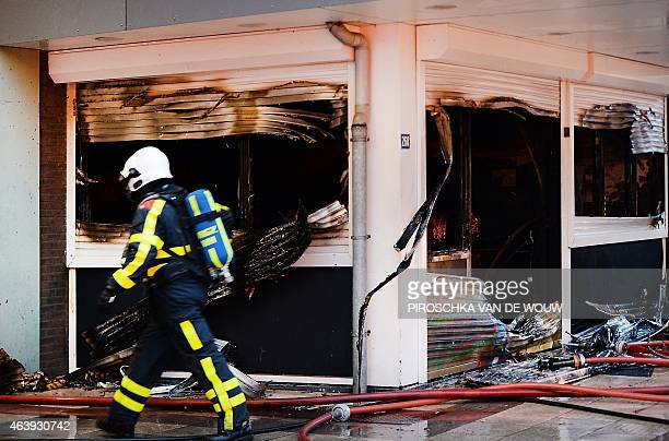 A firefighter walks past a burnt section of an apartment complex for the elderly after a fire broke out at the cafeteria in the Otto C Huismanstraat...