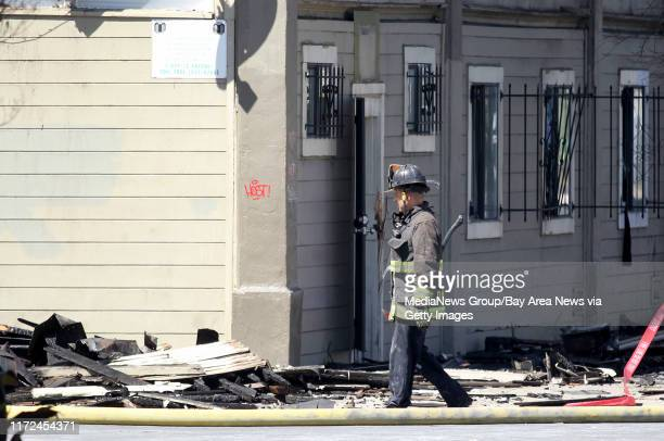 A firefighter walks past a West Oakland residential building gutted by a Monday fatal fouralarm fire along San Pablo Avenue in Oakland Calif on...