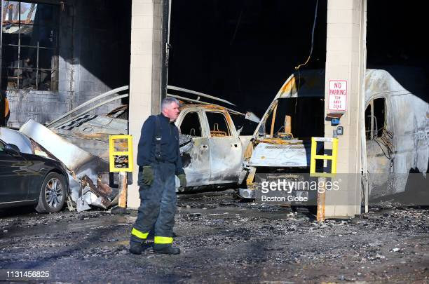 A firefighter walks past charred vehicles used to transport caskets inside a rear garage following a massive 9alarm fire that destroyed the New...