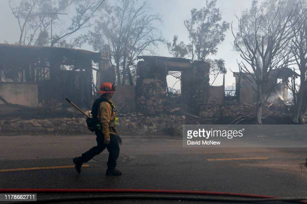A firefighter walks past houses burned by the Getty Fire on October 28 2019 in Los Angeles California Reported at 130 am the fire quickly burned 600...