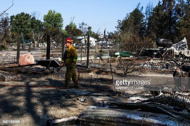 A firefighter walks through rubble after the Clayton Fire burned through Lower Lake California on August 16 2016 A man was arrested and charged with...