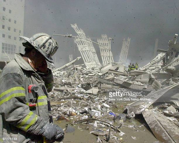 Firefighter walks through the rubble of the World Trade Center after it was struck by a commercial airliner in a terrorist attack. A hijacked...