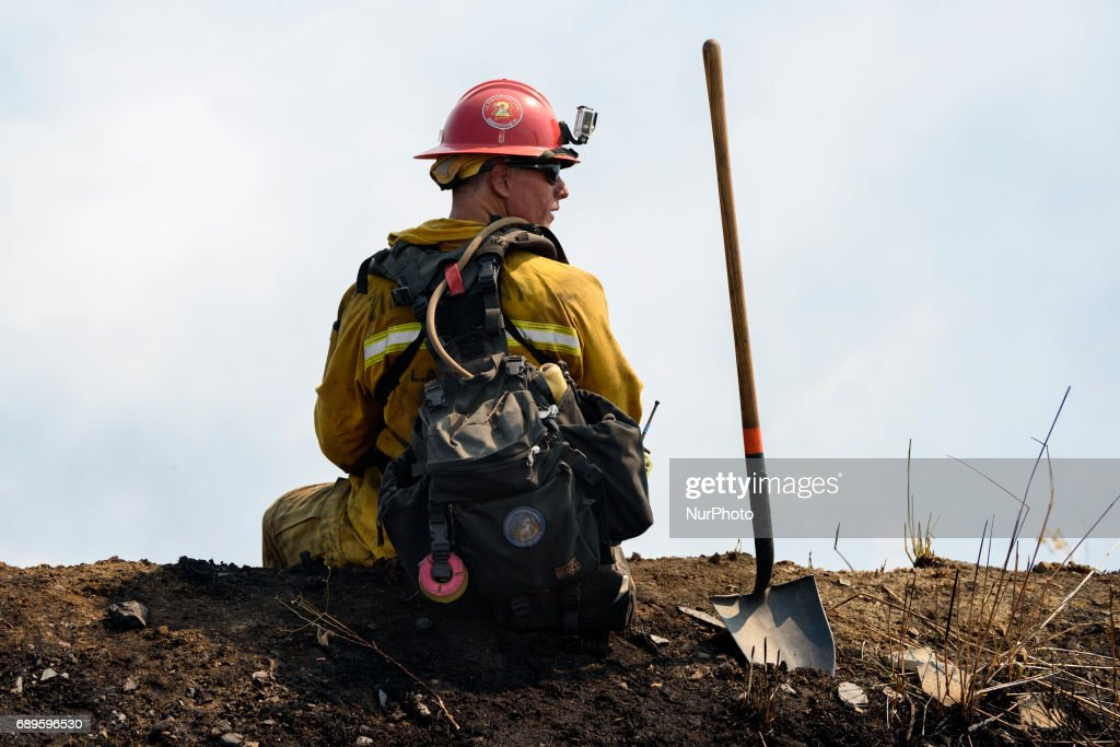 Firefighter watches a wildfire burning in Mandeville Canyon in Los Angeles, California on May 28, 2017. More than 150 firefighters battle the fire that burns near multi-million dollar homes in the Brentwood neighborhood.