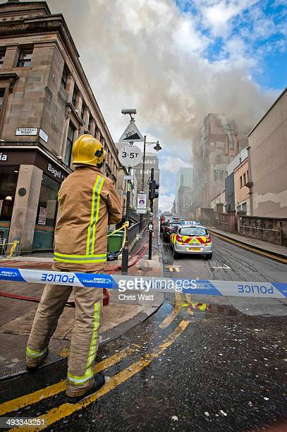 A firefighter watches as fire crews tackle a blaze at the Glasgow School of Art Charles Rennie Mackintosh Building on May 23 2014 in Glasgow Scotland...
