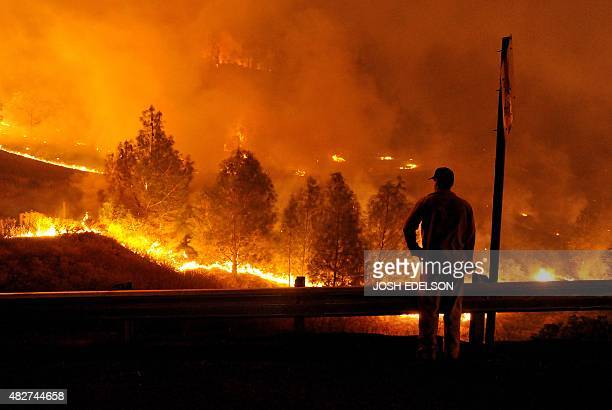 A firefighter watches as flames approach Highway 20 during the Rocky fire near Clear Lake California on August 2 2015 The fire has charred more than...