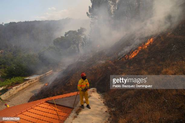 Firefighter watches flames approaching Mega Fundeira village after a wildfire took dozens of lives on June 20, 2017 near Picha, in Leiria district,...