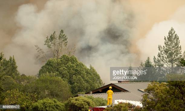 TOPSHOT A firefighter watches smoke billow as flames approach a residential area in Sonoma in California on October 10 2017 Firefighters battled...