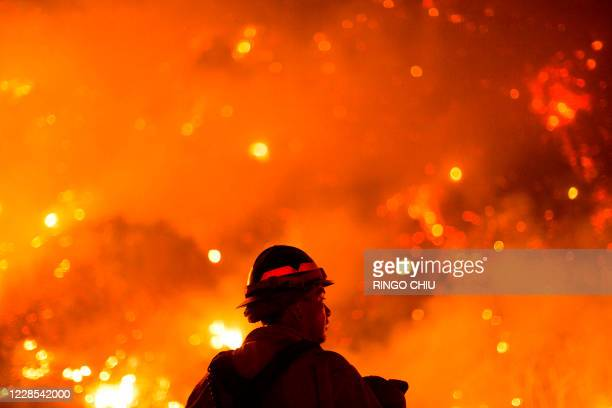 A firefighter watches the Bobcat Fire burning on hillsides near Monrovia Canyon Park in Monrovia California on September 15 2020 A major fire that...