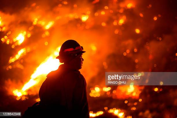 Firefighter watches the Bobcat Fire burning on hillsides near Monrovia Canyon Park in Monrovia, California on September 15, 2020. - A major fire that...
