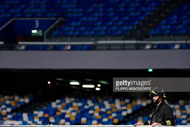A firefighter watches the Italian Cup semifinal second leg football match Napoli vs Inter Milan on June 13 2020 at the San Paolo stadium in Naples...