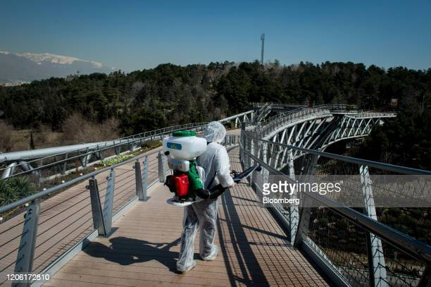 Firefighter wearing protective clothing, mask and goggles, sprays disinfectant on Tabia't bridge pedestrian overpass in Tehran, Iran, on Monday,...