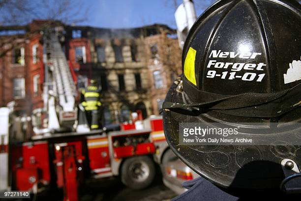 Firefighter wears his sentiments about the events of Sept 11 on his helmet as he helps to battle a threealarm fire on Macon St in the...