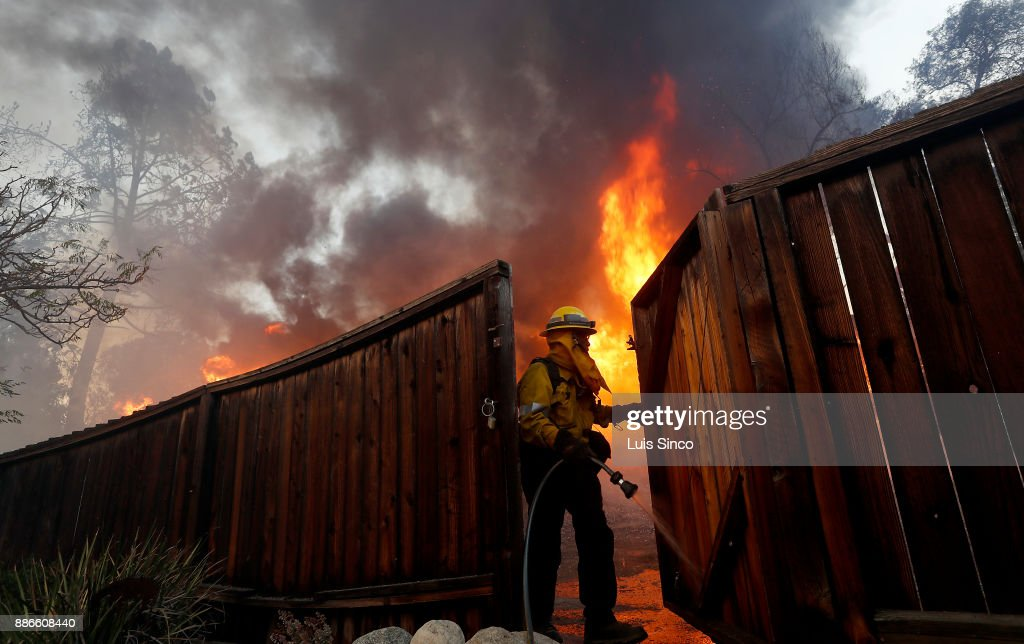 A firefighter wets down a fence to protect a house across the street from a residence that is engulfed in flames near the intersection of Johanna Avenue and McBroom Street in Shadow Hills on Tuesday, Dec. 5, 2017. The Creek Fire started at about 3:42 a.m. in the area of Gold Creek and Little Tujunga roads and has burned more than 11,000 acres.