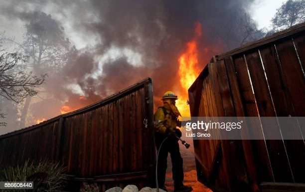 A firefighter wets down a fence to protect a house across the street from a residence that is engulfed in flames near the intersection of Johanna...