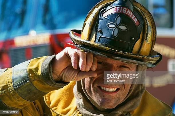firefighter wiping face - firefighter's helmet stock photos and pictures