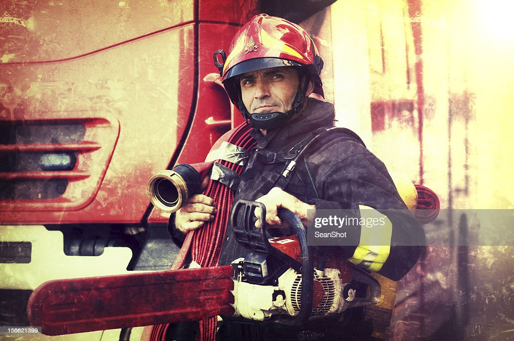Firefighter with chainsaw and fire hose in the Wings : Stock Photo