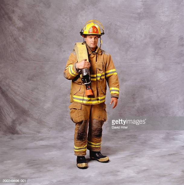 fire-fighter with fire hose over shoulder, (portrait) - fire protection suit - fotografias e filmes do acervo