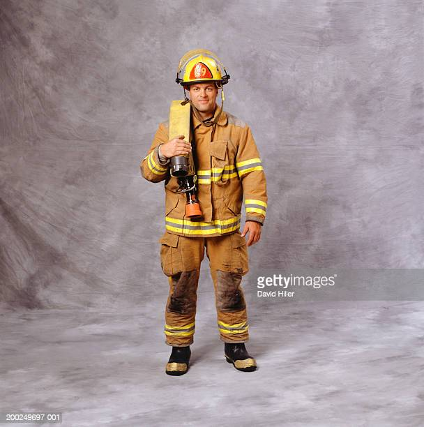 fire-fighter with fire hose over shoulder, (portrait) - fire protection suit stock pictures, royalty-free photos & images