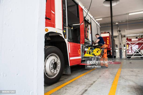 firefighter with fire truck equipmen - fire station stock photos and pictures