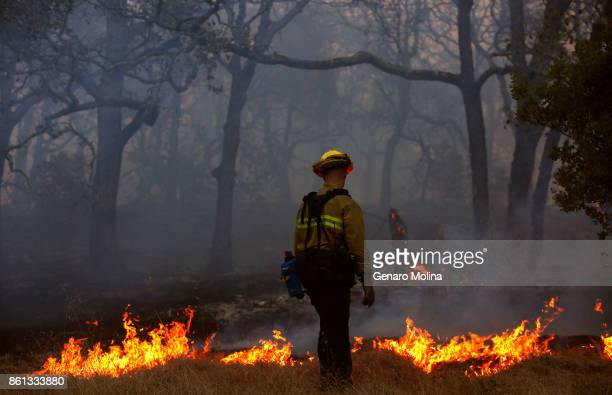 Firefighter with the Marin County Fire Department works a backfire in the Oakmont community along Highway 12 in Santa Rosa on October 13, 2017.