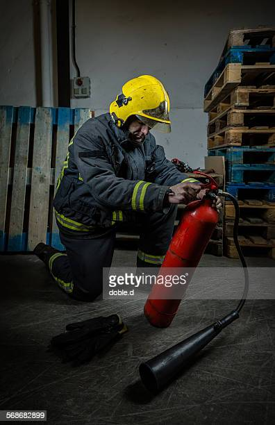 Firefighter with uniform reviewing extinguisher
