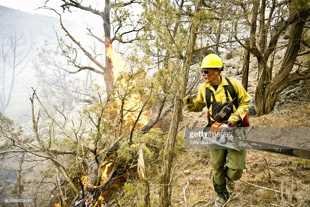 Firefighter working with chainsaw : Foto stock