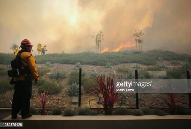Firefighter works as the Silverado Fire burns toward a home in Orange County on October 26, 2020 in Irvine, California. The fire has prompted...