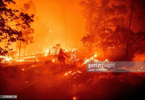Firefighter works the scene as flames push towards homes during the Creek fire in the Cascadel Woods area of unincorporated Madera County, California...