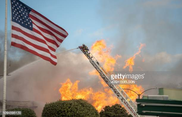 A firefighter works the scene as flames shoot into the air at an intersection in San Francisco California on February 6 2019 A gas line explosion in...