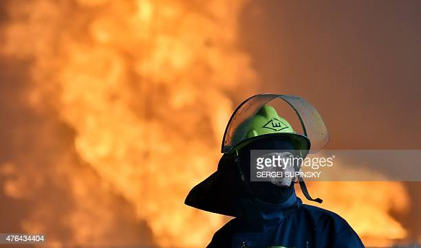 Firefighter works to bring under control a fire at an oil-storage facility in the village of Kryachki, some 30 kms from Kiev on June 9, 2015. Ukraine...