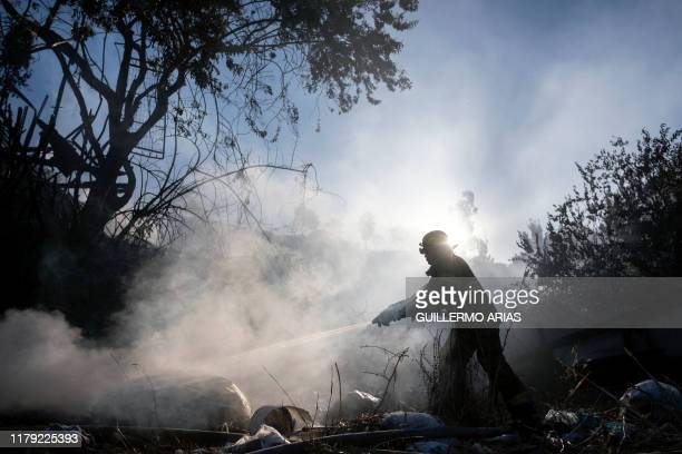 Firefighter works to extinguish a fire affecting two houses on a hillside at Camino Verde neighborhood in Tijuana, Baja California state, Mexico, on...