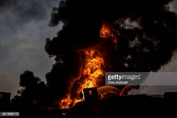 Firefighter works to extinguish an oil well set on fire by fleeing ISIS members on November 9, 2016 in Al Qayyarah, Iraq. Many families have begun...