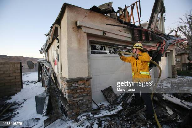 A firefighter works to put out a house fire caused by the Tick Fire on October 25 2019 in Canyon Country California The fire has burned 4300 acres...