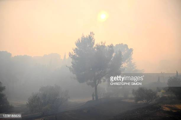 Firefighter works to put out a wildfire in Martigues, southeastern France, on August 24, 2020. - A major fire raged in the Bouches-du-Rhone region,...