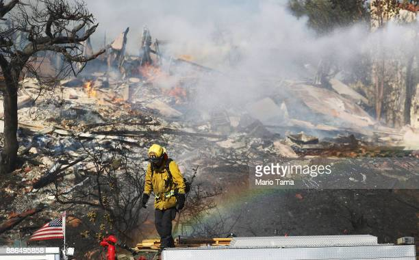A firefighter works while battling flames from the Thomas Fire in a residential neighborhood on December 5 2017 in Ventura California Around 45000...