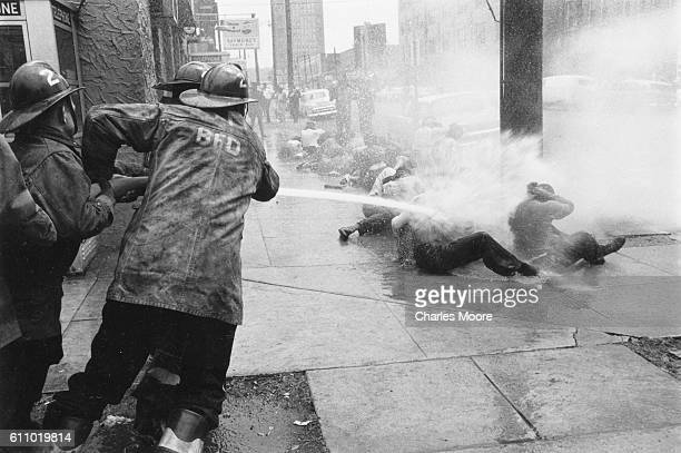 Firefighters aim firehoses at antisegregation demonstrators on a sidewalk on 17th Street North near Kelly Ingram Park Birmingham Alabama early May...
