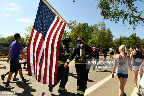 Firefighters Alec Shogan left and Jake Dickes middle with Boulder Rural Fire Department run with an American flagduring the 39th annual Bolder...
