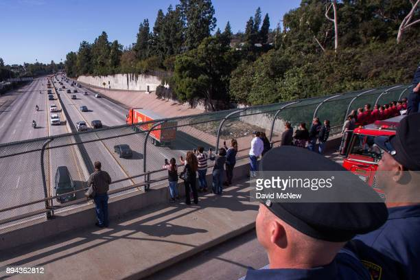 Firefighters and bystanders watch as a procession carries the body of Cory Iverson a fire engineer for Cal Fire San Diego who died fighting the...