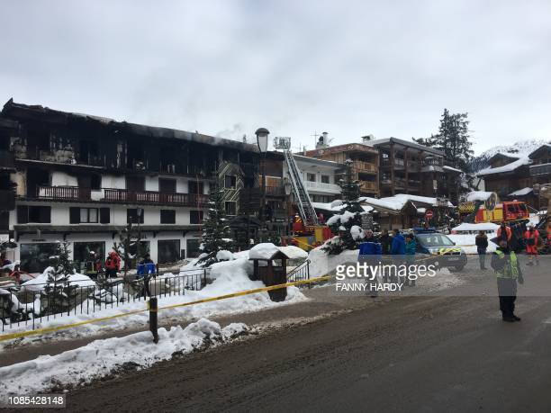 Firefighters and French gendarmes stand in front of a building destroyed by a major fire which killed two people and injured 22 more on January 20...